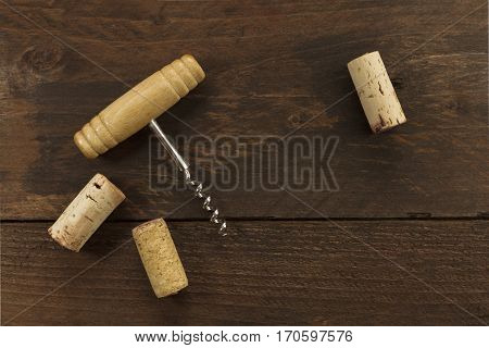A photo of an old-fashioned corkscrew with corks, shot from above on a dark wooden background texture with plenty of copy space. A design template for a wine list or a tasting invitation