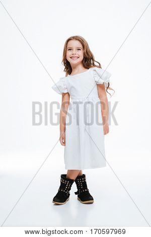 Full length of cheeful lovely little girl in dress standing over white background