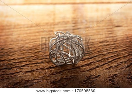 Sphere form from bent silver wire. Concept image for something tangled or complex. Shallow depth of field.