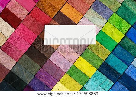 Cover for creative works. Spectrum of multi colored wooden blocks with blank white paper?label area. Background or cover for something creative or diverse.