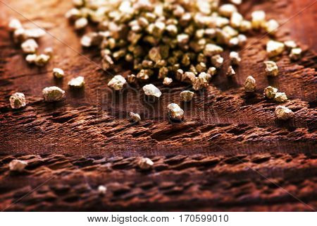 Mound of gold on a old grungy wooden work table.  Intentionally shot with extremely Shallow depth of field.