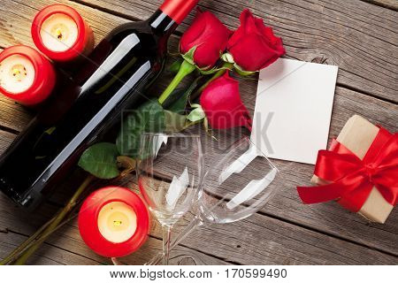 Valentines day greeting card, red rose flowers, wine and candles on wooden table. Top view with blank card for your text