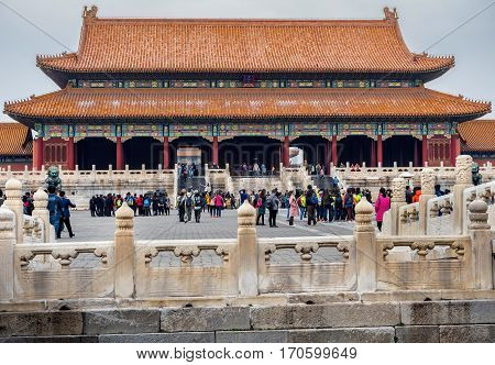 Beijing, China - Oct 30, 2016: Sculptured marble balustrades carved with dragon and phoenix motifs on Inner Golden River Bridges. In front is the Gate of Supreme Harmony (Taihemen), Forbidden City (Gu Gong, Palace Museum). A hazy day.