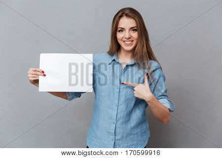 Woman in shirt pointing on blank board in second hand and looking at camera. Isolated gray background