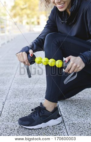 Personal trainer doing a myofascial massage with a foam roller