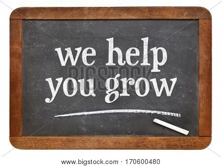 we help you grow blackboard sign - white chalk text on a vintage slate chalk board