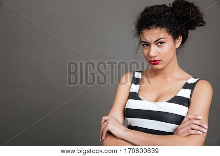 Irritated african american young woman standing with arms crossed over grey background