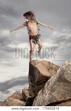 Wild man stands on a rock on grey sky background