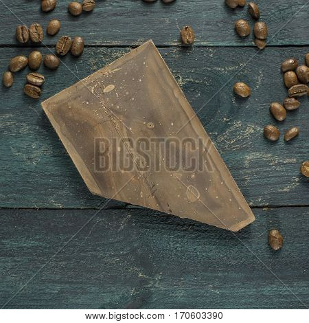 A square photo of artisan chocolate with coffee grains on a dark wooden boards texture, with copy space