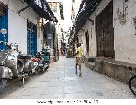 Zanzibar, Tanzania - July 14, 2016: Kid running in the centre of Stone town in Zanzibar, Tanzania, bikes on the backgorund