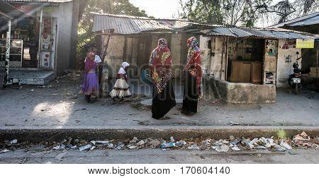 Zanzibar, Tanzania - July 14, 2016: Local folk of Zanzibar, muslim women in burkas and their kids, poor living