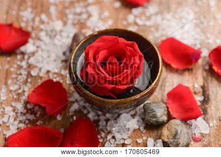 Roses petals with pile of salt ,stones and rose in bowl on old wooden board