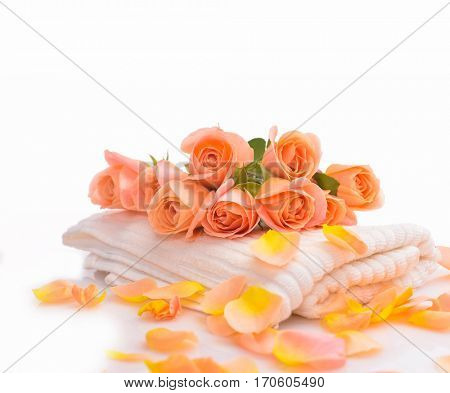 Spa setting with bouquet orange rose on towel with petals