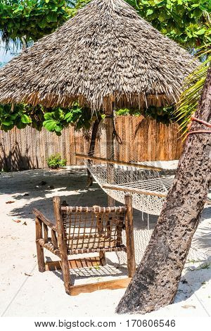 perfect place for rest on a beach with thatched umbrella, wooden chair and hammock near palm tree
