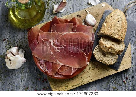 high-angle shot of an earthenware plate with some slices of spanish serrano ham, some slices of bread, a glass cruet with olive oil and some garlics, on a rustic gray wooden table