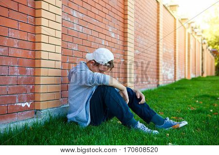 Sad Teenager sit by the Brick Wall outdoor