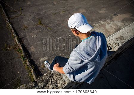 Depressed Teenager sit on the Roof Of Building