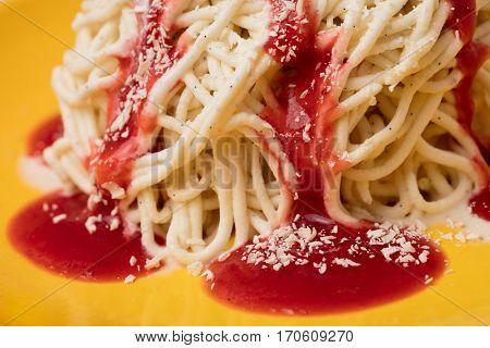 Homemade spaghetti ice cream with red strawberry sauce and white chocolate