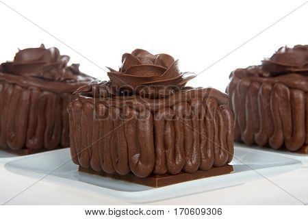 Three Square chocolate cake cupcakes on a chocolate candy bar frosted with frosting rose on top sitting on square white plates isolated on white background