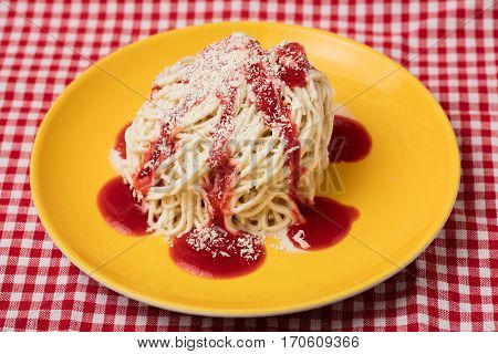 Homemade spaghetti ice cream with red strawberry sauce and white chocolate on a plate