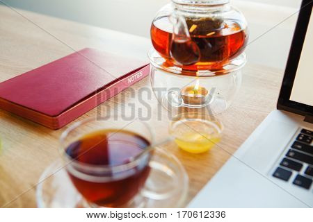 Hot brown tea in glass teapot, small cup honey and full cup with tea on glass saucer relax after working days. Open notebook and red diary lie on both sides of beverage.