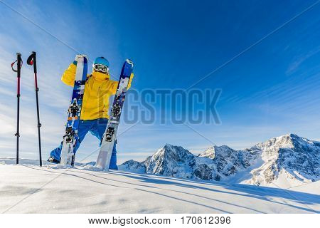 Mountaineer backcountry ski resting along a snowy ridge with skis in the backpack. In background blue sky and shiny sun and Ortler in South Tirol, Italy.  Adventure winter extreme sport.