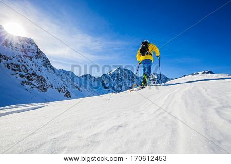 Mountaineer backcountry ski walking up along a snowy ridge with skis in the backpack. In background blue sky and shiny sun and Zebru, Ortler in South Tirol, Italy.  Adventure winter extreme sport.
