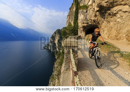 Mountain biking woman at sunrise over Lake Garda on path Sentiero della Ponale, Riva del Garda, Italy
