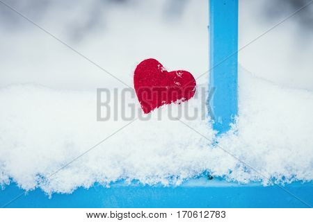 red heart in snow by blue fence closeup cold winter day