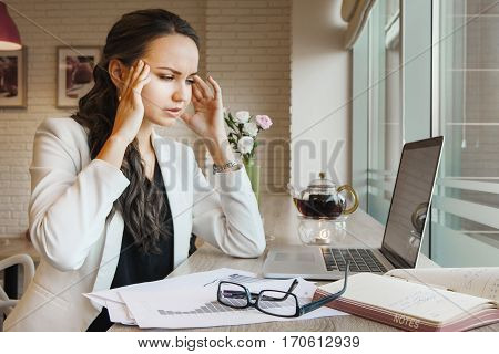 Woman holding hands at temples headache during work with charts, notebook and records in notes. Picture on brick wall, red lamp cover, daylight, green vase and teapot with candle on background.