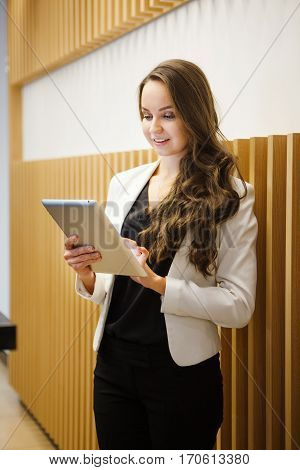 Brunette looking with interest in tablet. Woman dressed in black blouse, white jacket and black trousers. Girl with tablet computer in hands near wall