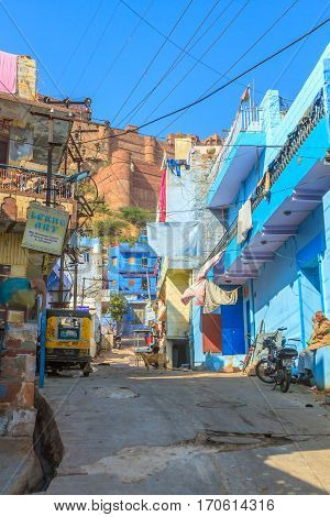 Jodhpur, India, 16th January 2017 - A sidestreet in Jodhpur with the Mehrangarh Fort in the background.
