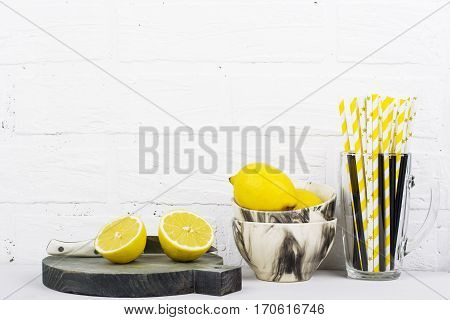 Kitchen still life monochrome colors, marble bowls, ceramic bowls, gray striped mug, wooden cutting board, juicy fresh lemons, kitchen tools on a background of a white brick wall. selective