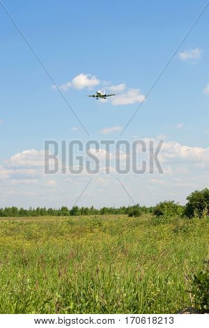 Passenger plane comes in to land over the summer field