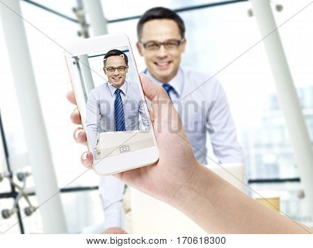 hand of a female holding a cellphone taking a picture of a smiling business man in office.