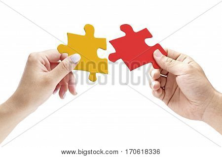 hands of a male and female putting together two matching jigsaw pieces isolated on white background.