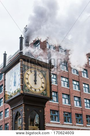 The historic steam clock strikes midday in Gastown downtown Vancouver with jets of steam rising from the clock
