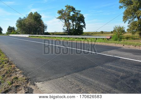 Laying new asphalt road. Close up on asphalt road repair.