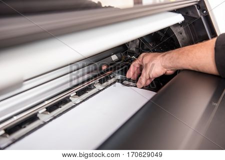 Man Setting The Printer To The Width Of The Paper