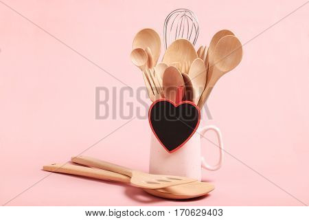Love and Cooking concept. Wooden kitchen utensils(spade of frying pan spoon fork ladle and whisk) in pink cup and black blank slate heart with space for text on pink background.