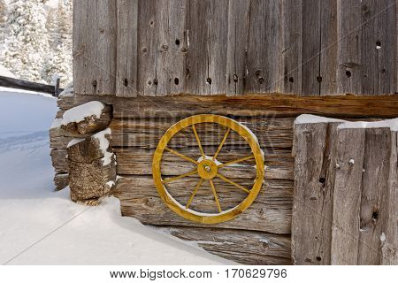 Old yellow wagon wheel hanging on wall to decorate rustic wooden barn wall with cold snow winter scene in Austria, Europe