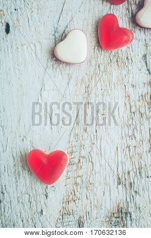 Red heart shape candy on a white rustic wooden table with space for text. Romantic love concept. Valentine's Day greetings card. Valentines theme. Top view. Copy space.