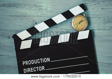 Clapperboard and old round clock lie on the painted board