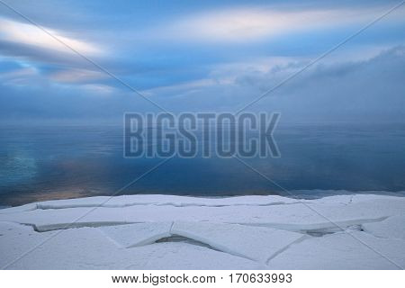 Winter landscape figured blocks of snow water covered with thin layers of ice and beautiful clouds