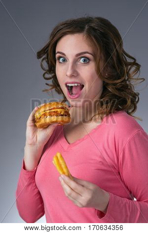 young beautiful girl with a sandwich and a French fries from a fast food smiling on a gray background