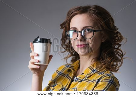 young beautiful girl in glasses with   cup of coffee from a fast food smiling on a gray background