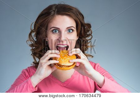 young beautiful girl with a sandwich from a fast food opened her mouth to take a bite on a gray background