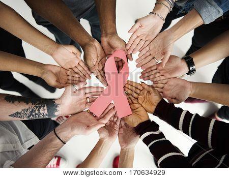 Human hands together holding cancer symbol