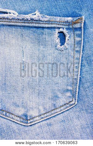 Back pocket of blue ripped jeans denim texture