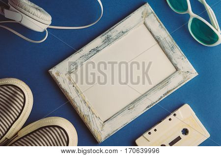 Audio cassette and headphones on a blue background. Mock up